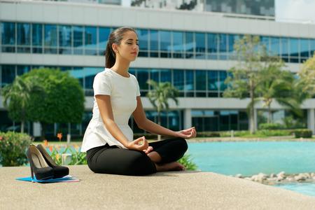 descansando: Young destac� mujer de negocios hispano haciendo yoga fuera del edificio de la oficina, sentado en posici�n de loto con las manos en las rodillas en la calle. Concepto de largas horas de trabajo y la necesidad de vacaciones sin estr�s