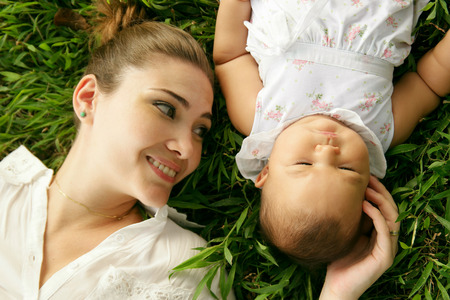 caresses: Young woman with her little daughter, relaxing on grass in park. The mom touches her toddler head and caresses her smiling. High angle view, closeup