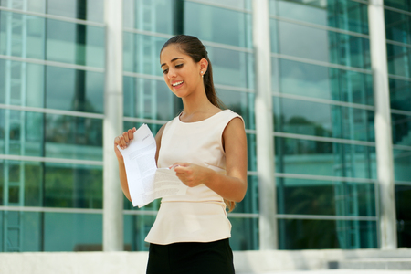 Portrait of beautiful latina businesswoman resigns from job, tearing an employment contract and smiling. The lady is standing in front of a modern office building. photo