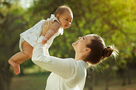 Beautiful woman lifts high her adorable baby up mid air and looks at her smiling. Happy parent spending time playing with daughter in park at sunset. Medium shot Stock Photo