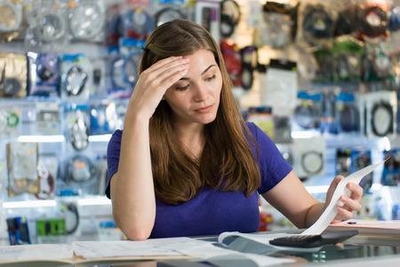 cuenta: Joven empresario blanco hembra dirige una pequeña empresa y trabajar en tienda de informática, que controla cuentas y facturas con expresión preocupada Foto de archivo
