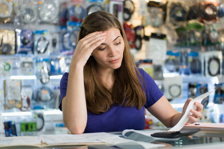 stressed business woman: Young white female entrepreneur running a small business and working in computer shop, checking bills and invoices with worried expression Stock Photo