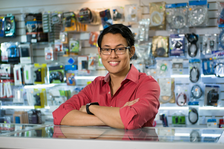 Portrait of young chinese man working as clerk in computer and technology store, smiling at camera and leaning on desk in shop Standard-Bild