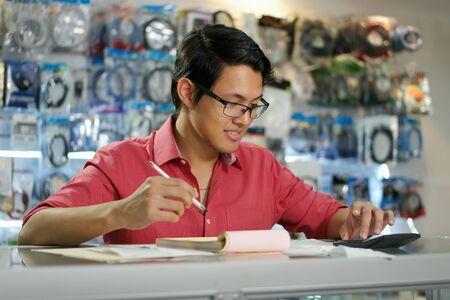 Joven empresario asiático ser propietario de una tienda de informática y comprobar las facturas y facturas con la calculadora, hacer el presupuesto y la revisión de los gastos.