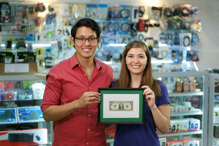 business success: People running small family business, with asian shop owner and caucasian wife in computer store, showing their first dollar to the camera and smiling