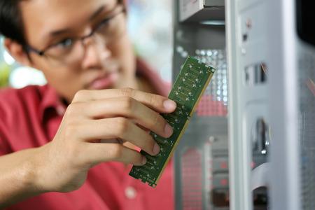 Joven dueño de una tienda asiática trabaja en almacén de la computadora, que repara el ordenador y la adición de ram para PC. Enfoque en la mano que sostiene el banco de memoria RAM