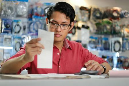 revisando documentos: Joven empresario asiático ser propietario de una tienda de informática y comprobar las facturas y facturas con la calculadora, hacer el presupuesto y la revisión de los gastos.