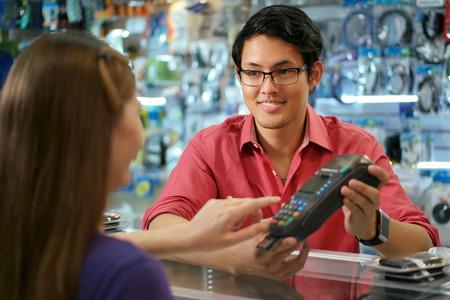 Mujer joven que paga con tarjeta de crédito en la tienda de informática, con el empleado de ventas asiáticas sonriendo y sosteniendo pos. La chica entra código de seguridad y espera para la recepción