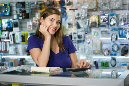 electronic store: Young white female entrepreneur running a small business and working in a computer shop, and checking bills and invoice with calculator, doing budget and reviewing expenses.