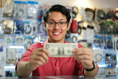 Young asian shop owner in computer store, showing his first dollar to the camera and smiling. Focus on face