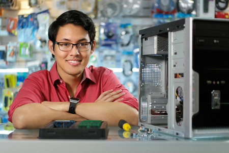 man working on computer: Young asian shop owner working in computer store, repairing computer and adding ram to pc. Portrait of man smiling at camera Stock Photo