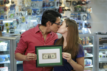 People running small family business, with asian shop owner and caucasian wife in computer store, showing their first dollar to the camera and kissing