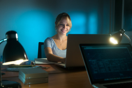 Beautiful woman working as interior designer, staying late at night in office with drawings and laptop computer to complete a project. The girl gets an idea and smiles. Stock Photo