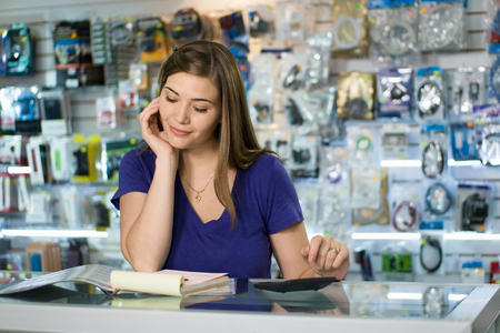 Jonge witte vrouwelijke ondernemer het runnen van een klein bedrijf en werken in een computer winkel, en het controleren van rekeningen en facturen met een rekenmachine, doet de begroting en de herziening van de uitgaven.