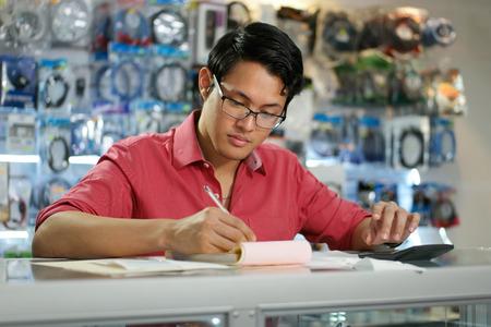 Jonge Aziatische ondernemer bezit van een computer winkel en het controleren van rekeningen en facturen met een rekenmachine, doet de begroting en de herziening van de belastingen.