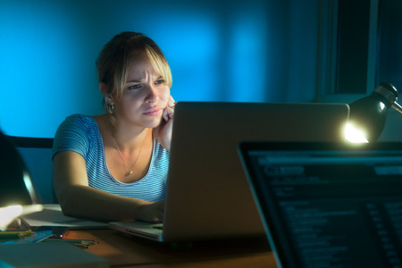 Beautiful woman working late at night, looking at laptop monitor with hand on chin, having problems to understand what she sees.
