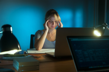 exhausted worker: Beautiful woman working as interior designer staying late at night in office with drawings and laptop computer. The girl feels tired and her eyes hurt. Stock Photo