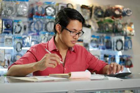 revisando documentos: Joven empresario asiático ser propietario de una tienda de informática y comprobar las facturas y facturas con la calculadora haciendo el presupuesto y la revisión de los gastos. Foto de archivo