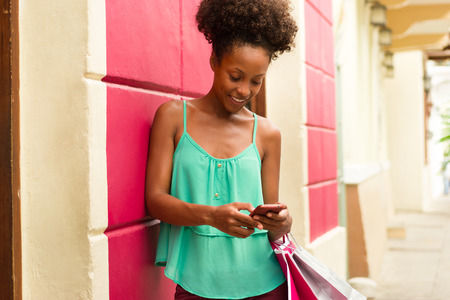 mobile shopping: Black woman in Casco Antiguo - Panama City with shopping bags. The girl leans on a wall and types message with her phone on social network. Stock Photo