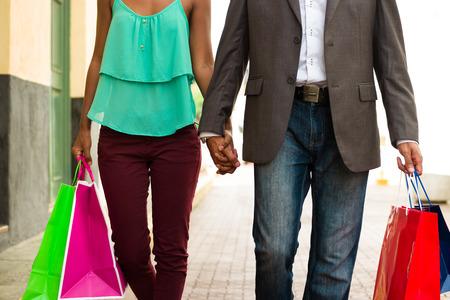 parejas caminando: Tur�stica Negro pareja heterosexual caminar en las calles del Casco Antiguo de la Ciudad de Panam� con bolsas de la compra. Recorta la vista de hombre y mujer tomados de la mano