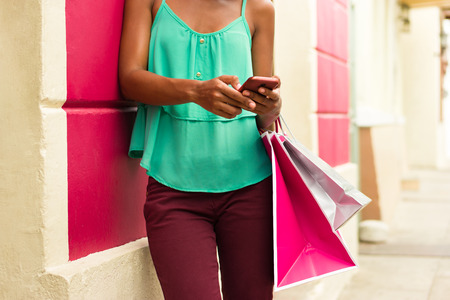 phone conversations: Black woman in Casco Antiguo - Panama City with shopping bags. The girl leans on a wall and types message with her phone on social network. Stock Photo