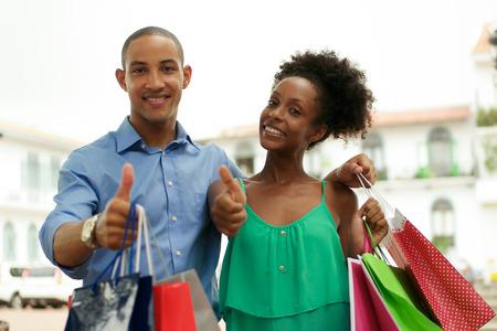 Portrait des schwarzen Touristenheterosexuellen Paar in Casco Antiguo - Panama-Stadt mit Einkaufstaschen. Der Mann und seine Freundin Lächeln in die Kamera macht ok Zeichen
