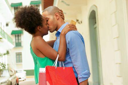 besos hombres: Turística Negro pareja heterosexual en Casco Antiguo - Ciudad de Panamá con bolsas de la compra. La niña celebrar una tarjeta de crédito y besa a su novio Foto de archivo