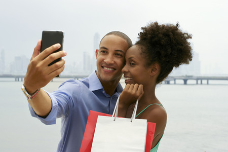african lady: Black tourist heterosexual couple in Casco Antiguo Panama City with shopping bags. The man takes a selfie with his girlfiend and shopping bags with skyline in background