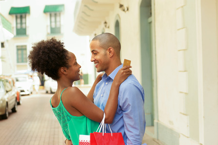 woman holding card: Black tourist heterosexual couple in Casco Antiguo - Panama City with shopping bags. The girl hold a credit card and looks at her boyfriend Stock Photo