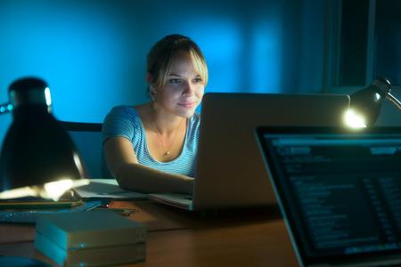 美しい女性は事務所で夜遅くまで働く、web サーフィンとラップトップ コンピューターを持つ社会的なネットワークの記事を書きます。女の子笑顔な