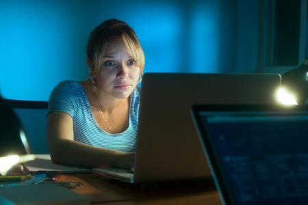 Beautiful woman working late at night in office, surfing the web and reading a post on social network with laptop computer. The girl looks at the screen with scared expression