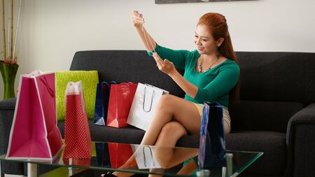contemplates: Young latina woman back at home after shopping, surrounded by bags on sofa. She contemplates a necklace and smiles for joy for her new purchase Stock Photo