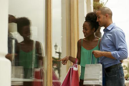 compras: Retrato de turismo negro pareja heterosexual en la Ciudad de Panamá con bolsas de la compra. El hombre y su novia miran escaparate Foto de archivo
