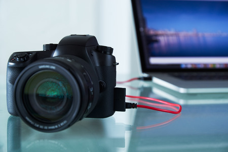 Still life of dslr camera connected with USB cable to laptop computer on glass table. The photo camera is transferring images to PC in background. Copy space
