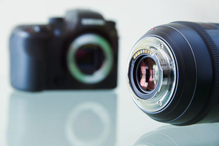 dslr camera: Still life of dslr camera and photo lens on glass table. Closeup of electronic circuit, rear glass and mount with copyspace in foreground