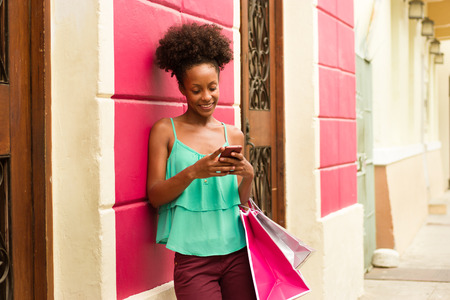 shopping scenes: African American woman in Casco Antiguo - Panama City with shopping bags. The girl leans on a wall and types message with her phone on social network. Stock Photo