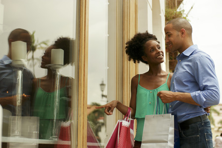 Portret van zwarte toeristische heteroseksueel paar in Panama City met boodschappentassen. De man en zijn vriendin kijken naar etalage