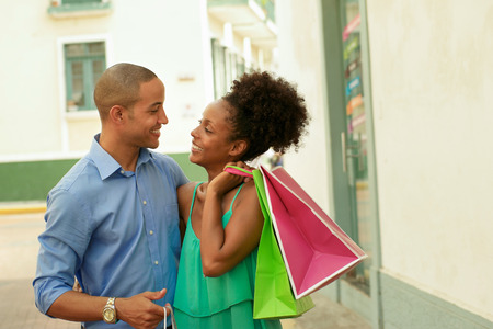 african america: Portrait of black tourist heterosexual couple in Casco Antiguo - Panama City with shopping bags. The man and his girlfriend smile at the camera