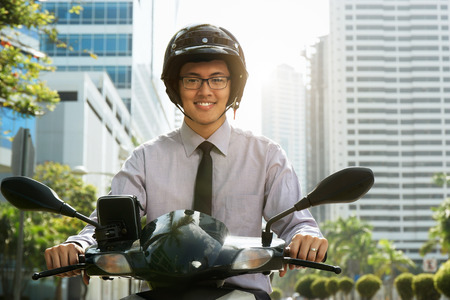 medium shot: Young asian businessman commuting to job. The man rides a motorcycle scooter with white helmet and smiles at camera