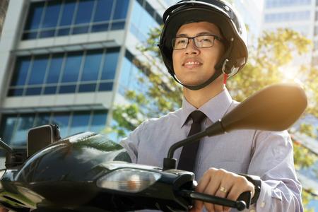 Joven empresario asiático desplazamientos al trabajo por la mañana. El hombre monta una moto motocicleta con casco blanco y mira hacia otro lado