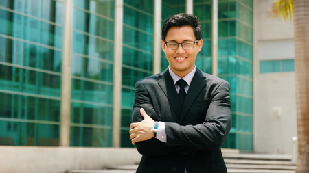 Portrait of happy and confident young asian businessman. The man stands in a street against office buildings and crosses arms looking at camera