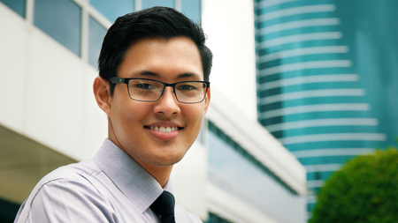 people street: Portrait of happy and confident young asian businessman. The man stands in a street against office buildings and crosses arms looking at camera