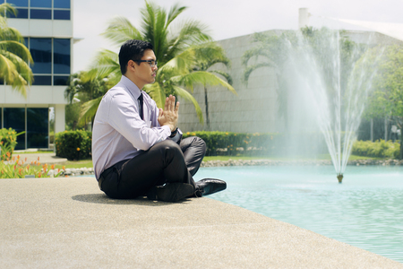 prayer: Asian businessman relaxing outside office building. The man does yoga on a bridge and smiles with eyes closed in prayer position Stock Photo