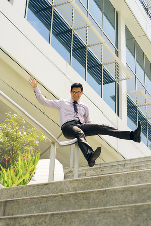 handrail: Young and happy chinese businessman sliding downstairs on rails of office staircase. The man enjoys his new promotion at job