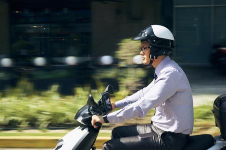 Joven empresario asiático desplazamientos al trabajo. El hombre monta una motocicleta con el casco blanco. Movimiento fondo borroso