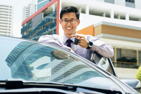 Young adult chinese businessman holds keys of new car, leaning on auto door. He smiles and looks proud at camera, showing the keys. Waist up portrait