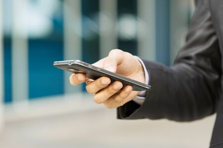 mobile communication: Closeup of businessman typing note on mobile phone. The man writes on his smartphone using one hand with office building in background.