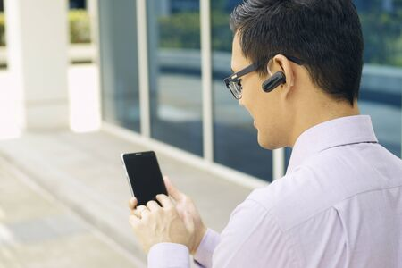 phone number: Young chinese businessman typing phone number on smartphone and talking with  headset device