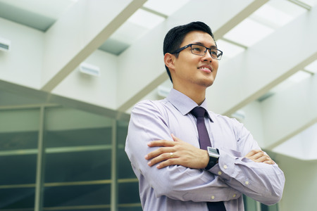 good guys: Portrait of happy and confident young asian businessman. The man stands in a street against office buildings and crosses arms looking away