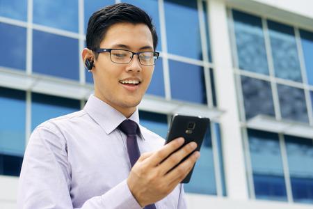 Jonge Chinese zakenman doet video conference call op smartphone en praten met bluetooth headset apparaat in de straat